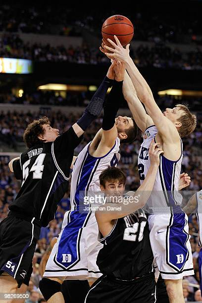 Matt Howard and Gordon Hayward of the Butler Bulldogs fight for a rebound in the second half against Brian Zoubek and Kyle Singler of the Duke Blue...