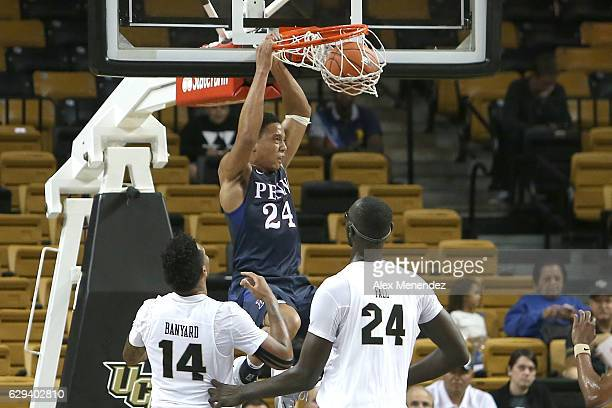 Matt Howard of the Pennsylvania Quakers slam dunks the ball in front of Nick Banyard and Tacko Fall of the UCF Knights during an NCAA basketball game...