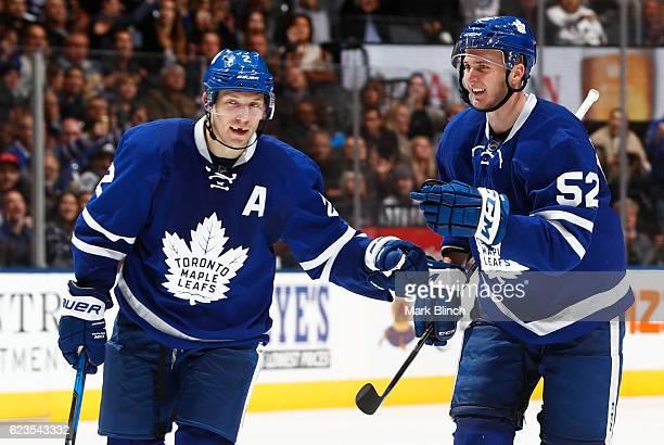 Matt Hunwick and teammate Martin Marincin of the Toronto Maple Leafs celebrate a goal by against the Nashville Predators by Leo Komarov of the...