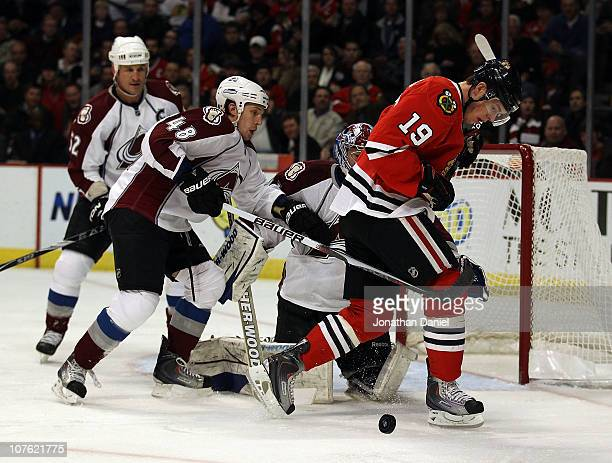 Matt Hunwick of the Colorado Avalanche knocks the puck away from Jonathan Toews of the Chicago Blackhawks in front of teammate Craig Anderson at the...