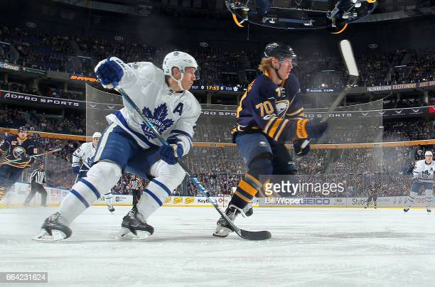 Matt Hunwick of the Toronto Maple Leafs and Alexander Nylander of the Buffalo Sabres playing in his first NHL game follow the puck during an NHL game...