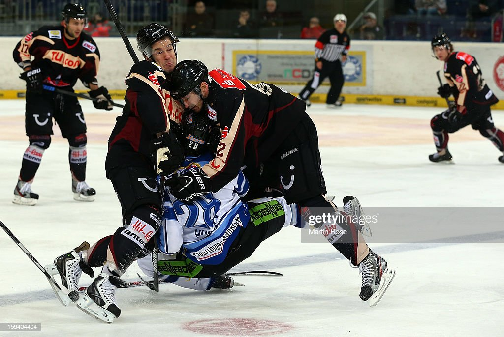 Matt Hussey (C) of Straubing is checked by Sergej Janzen (L) and Sachar Blank (R) of Hannover during the DEL match between Hannover Scorpions and Straubing Tigers at TUI Arena on January 13, 2013 in Hanover, Germany.
