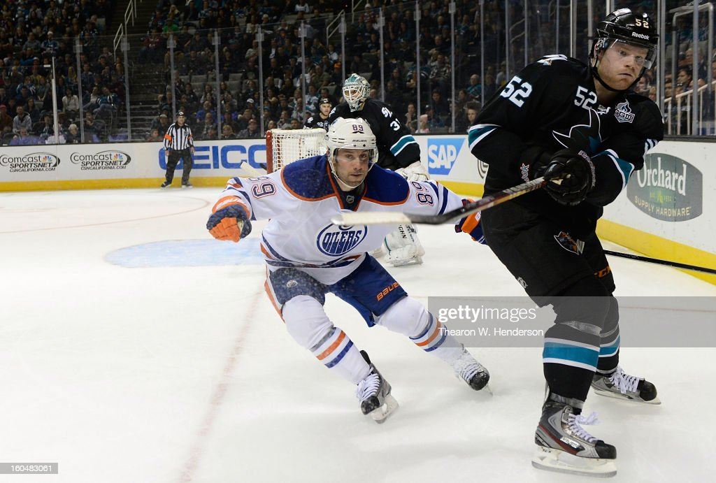 Matt Irwin #52 of the San Jose Sharks passes the puck around the boards defended by Sam Gagner #89 of the Edmonton Oilers at HP Pavilion on January 31, 2013 in San Jose, California.