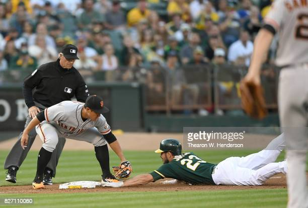 Matt Joyce of the Oakland Athletics gets tagged out at third base by JaeGyun Hwang of the San Francisco Giants in the bottom of the first inning at...