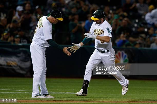 Matt Joyce of the Oakland Athletics is congratulated by acting third base coach Steve Scarsone after hitting a home run against the Houston Astros...