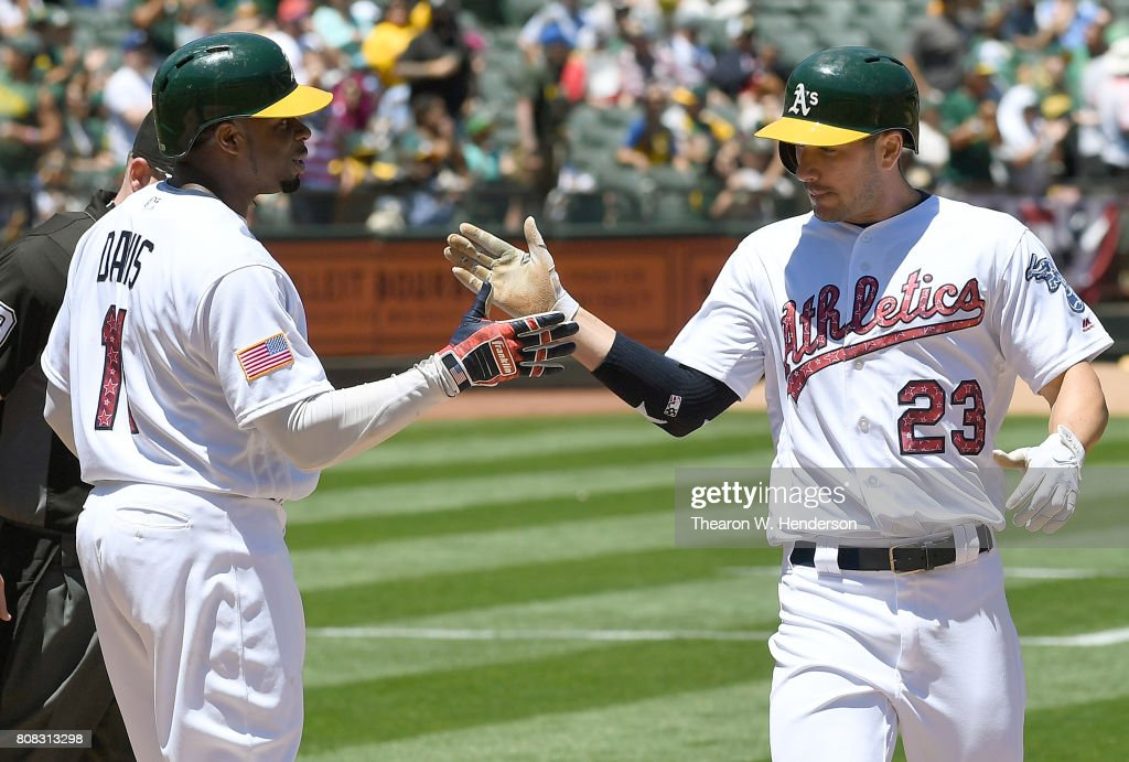 Matt Joyce #23 of the Oakland Athletics is congratulated by Rajai Davis #11 after Joyce hit a two-run homer against the Chicago White Sox in the bottom of the third inning at Oakland Alameda Coliseum on July 4, 2017 in Oakland, California.