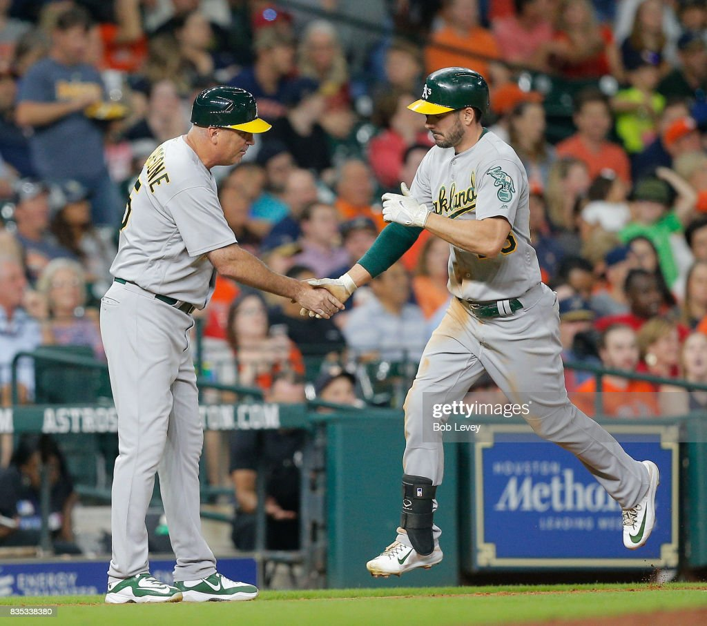 Matt Joyce #23 of the Oakland Athletics is congratulated by third base coach Steve Scarsone #15 after hitting a home run in the eighth inning against the Houston Astros at Minute Maid Park on August 18, 2017 in Houston, Texas.