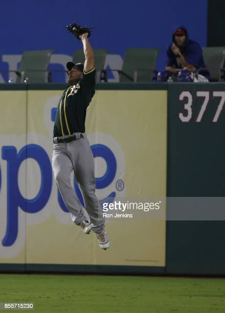 Matt Joyce of the Oakland Athletics jumps to catch a deep ball off the bat of ShinSoo Choo of the Texas Rangers during the eighth inning at Globe...