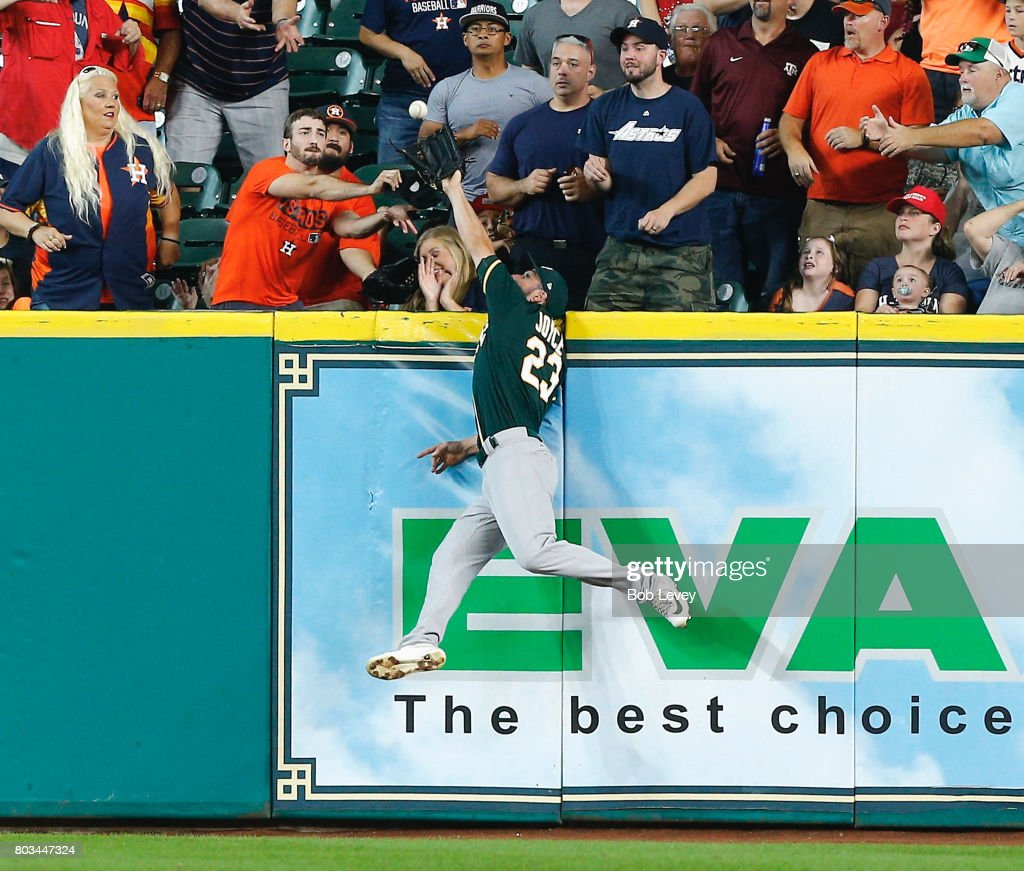 Matt Joyce #23 of the Oakland Athletics makes a leaping catch at the wall on fly ball by Josh Reddick #22 of the Houston Astros in the first inning at Minute Maid Park on June 29, 2017 in Houston, Texas.