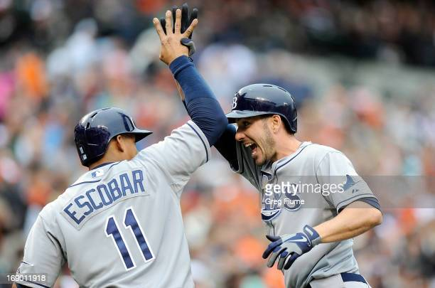 Matt Joyce of the Tampa Bay Rays celebrates with Yunel Escobar after hitting a home run in the third inning against the Baltimore Orioles at Oriole...