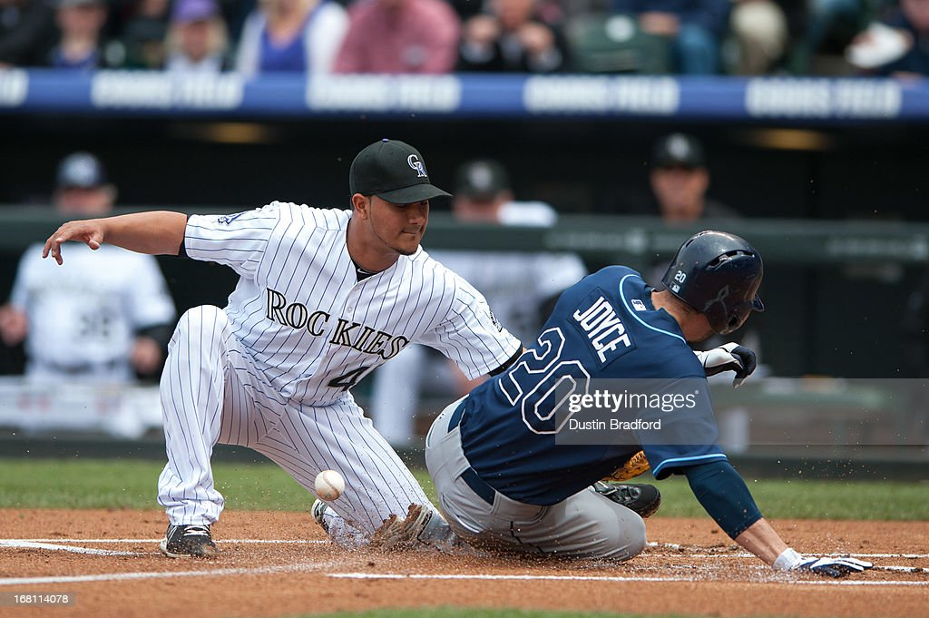 Matt Joyce of the Tampa Bay Rays scores on a wild pitch by Jhoulys Chacin of the Colorado Rockies despite a tag attempt by Chacin in the first inning...
