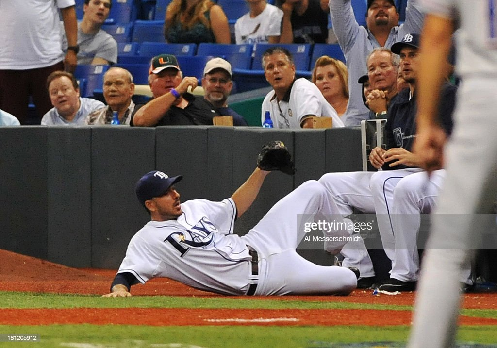 Matt Joyce #20 of the Tampa Bay Rays slides into the dugout attempting to catch a foul ball against the Texas Rangers September 19, 2013 at Tropicana Field in St. Petersburg, Florida. Texas won 8 - 2.