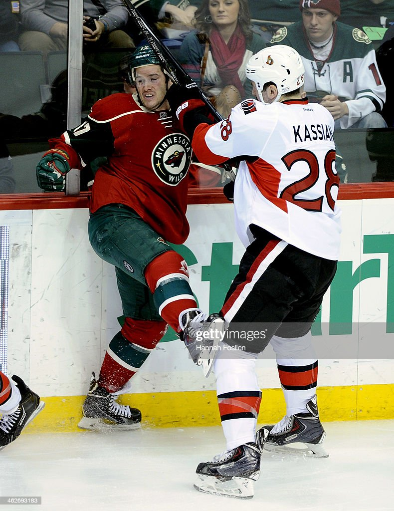 Matt Kassian of the Ottawa Senators checks Torrey Mitchell of the Minnesota Wild into the boards during the first period of the game on January 14...