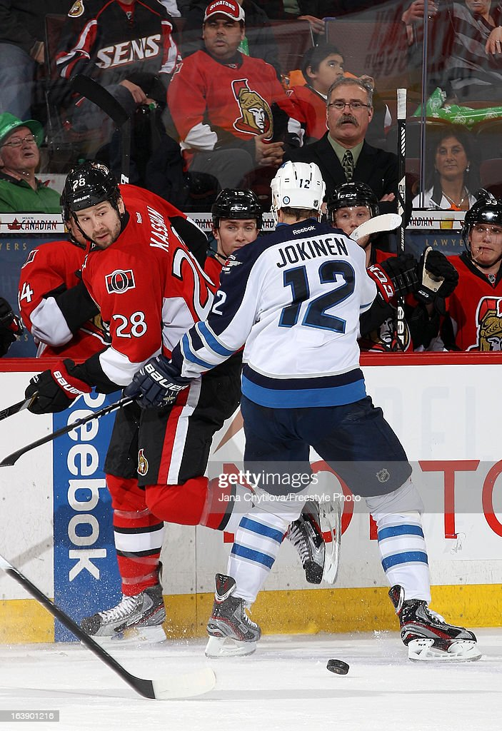 Matt Kassian #28 of the Ottawa Senators chips the puck past Olli Jokinen #12 of the Winnipeg Jets during an NHL game at Scotiabank Place, on March 17, 2013 in Ottawa, Ontario, Canada.