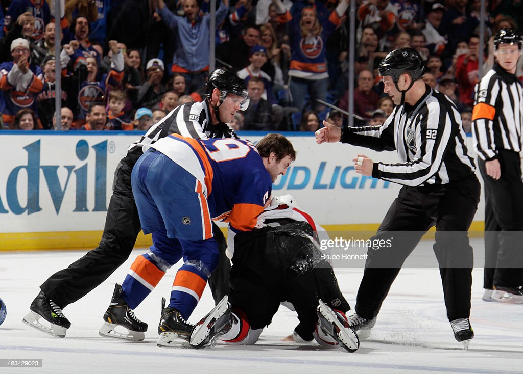 Matt Kassian of the Ottawa Senators falls to the ice while fighting with Brett Gallant of the New York Islanders in the first period at the Nassau...