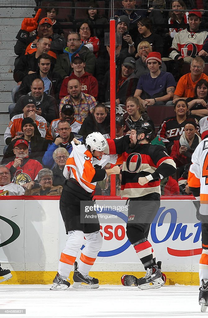 Matt Kassian of the Ottawa Senators fights with Jay Rosehill of the Philadelphia Flyers at Canadian Tire Centre on December 9 2013 in Ottawa Ontario...