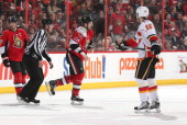 Matt Kassian of the Ottawa Senators gets fired up after a first period fight as Brian McGrattan of the Calgary Flames and teammate Jason Spezza look...