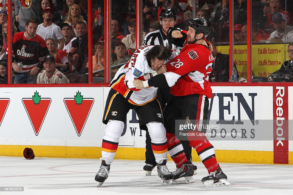 Matt Kassian of the Ottawa Senators throws a punch in a fight against Kevin Westgarth of the Calgary Flames during an NHL game at Canadian Tire...