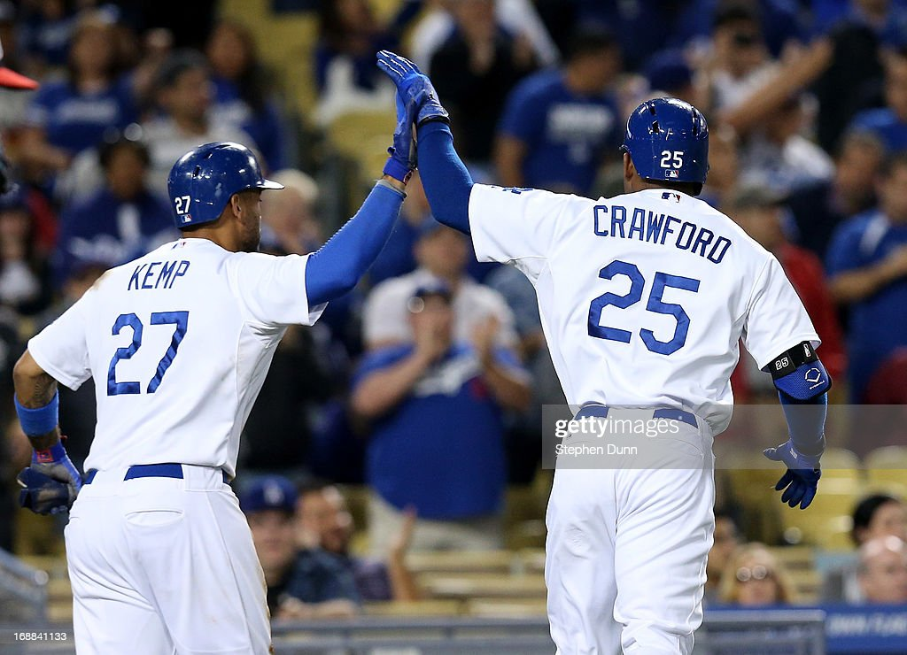 <a gi-track='captionPersonalityLinkClicked' href=/galleries/search?phrase=Matt+Kemp&family=editorial&specificpeople=567161 ng-click='$event.stopPropagation()'>Matt Kemp</a> #27 and <a gi-track='captionPersonalityLinkClicked' href=/galleries/search?phrase=Carl+Crawford&family=editorial&specificpeople=208074 ng-click='$event.stopPropagation()'>Carl Crawford</a> #25 of the Los Angeles Dodgers celebrate after Kemp scored on Crawford's sacrifice fly in the eighth inning against the Washington Nationals at Dodger Stadium on May 15, 2013 in Los Angeles, California. The Dodgers won 3-1.