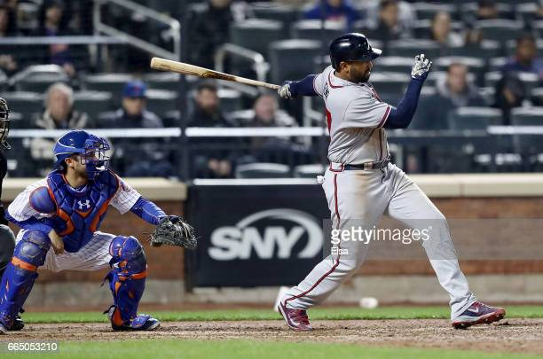 Matt Kemp of the Atlanta Braves hits the game winning 2 RBI double as Travis d'Arnaud of the New York Mets defends in the 12th inning on April 5 2017...
