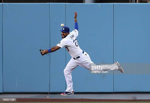 Matt Kemp of the Los Angeles Dodgers can't get the ball hit off the wall by Eric Young Jr#1 of the Colorado Rockies who turns the play into an inside...