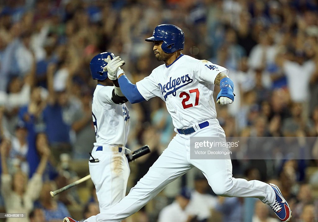 Matt Kemp #27 of the Los Angeles Dodgers celebrates with teammate Dee Gordon #9 after Kemp scored on a sacrifice fly Justin Turner #10 (not in photo) in the seventh inning during the MLB game against the Detroit Tigers at Dodger Stadium on April 8, 2014 in Los Angeles, California.