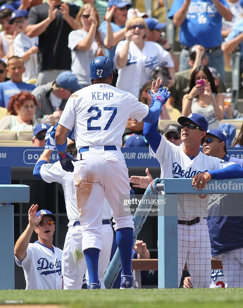 Matt Kemp #27 of the Los Angeles Dodgers gets a high-five from manager Don Mattingly after scoring in the first inning off a single to center by Adrian Gonzalez #23 (not in photo) against Pittsburgh Pirates during the MLB game at Dodger Stadium on April 7, 2013 in Los Angeles, California.