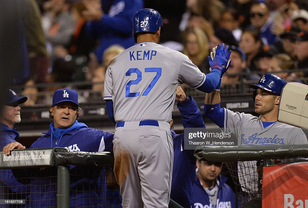 <a gi-track='captionPersonalityLinkClicked' href=/galleries/search?phrase=Matt+Kemp&family=editorial&specificpeople=567161 ng-click='$event.stopPropagation()'>Matt Kemp</a> #27 of the Los Angeles Dodgers is congratulated by manager <a gi-track='captionPersonalityLinkClicked' href=/galleries/search?phrase=Don+Mattingly&family=editorial&specificpeople=204707 ng-click='$event.stopPropagation()'>Don Mattingly</a> (L) and <a gi-track='captionPersonalityLinkClicked' href=/galleries/search?phrase=Skip+Schumaker&family=editorial&specificpeople=640599 ng-click='$event.stopPropagation()'>Skip Schumaker</a> #55 (R) after Kemp scored on a sacrifice fly during the six inning against the San Francisco Giants at AT&T Park on September 25, 2013 in San Francisco, California.