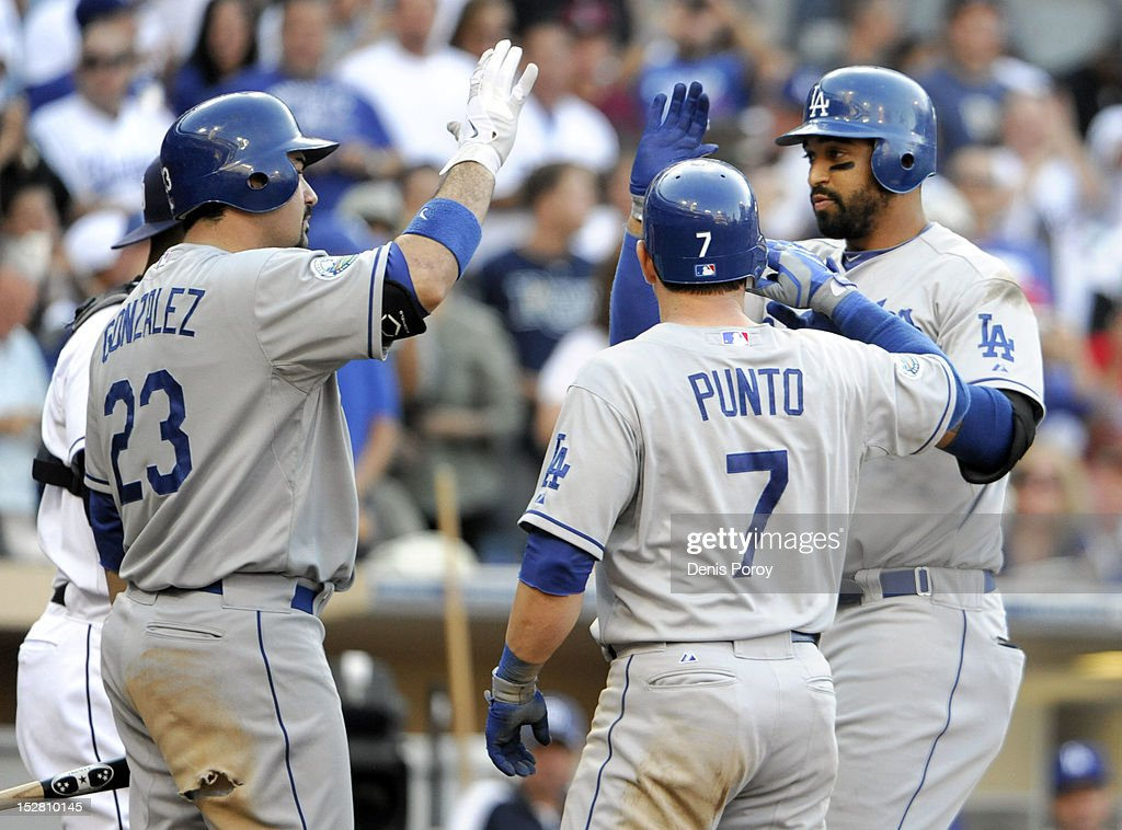 <a gi-track='captionPersonalityLinkClicked' href=/galleries/search?phrase=Matt+Kemp&family=editorial&specificpeople=567161 ng-click='$event.stopPropagation()'>Matt Kemp</a> #27 of the Los Angeles Dodgers, right, is congratulated by Adrian Gonzalez #23, left, and <a gi-track='captionPersonalityLinkClicked' href=/galleries/search?phrase=Nick+Punto&family=editorial&specificpeople=547246 ng-click='$event.stopPropagation()'>Nick Punto</a> #7, center, after he hit a two-run homer during the sixth inning of a baseball game against the San Diego Padres at Petco Park on September 26, 2012 in San Diego, California.