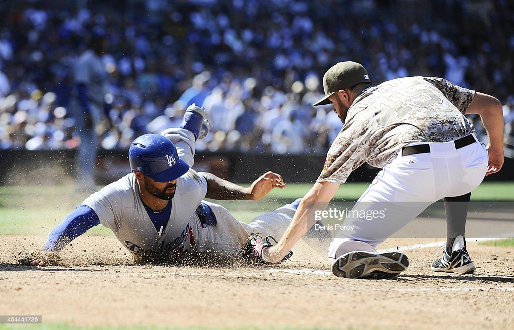 <a gi-track='captionPersonalityLinkClicked' href=/galleries/search?phrase=Matt+Kemp&family=editorial&specificpeople=567161 ng-click='$event.stopPropagation()'>Matt Kemp</a> #27 of the Los Angeles Dodgers scores ahead of the tag of <a gi-track='captionPersonalityLinkClicked' href=/galleries/search?phrase=Jesse+Hahn&family=editorial&specificpeople=12495165 ng-click='$event.stopPropagation()'>Jesse Hahn</a> #45 of the San Diego Padres during the eighth inning of a baseball game at Petco Park August, 31, 2014 in San Diego, California.