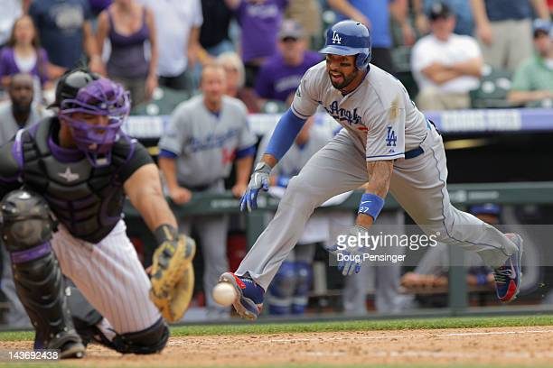 Matt Kemp of the Los Angeles Dodgers slides home to score behind catcher Wilin Rosario of the Colorado Rockies on a double by Dee Gordon of the Los...
