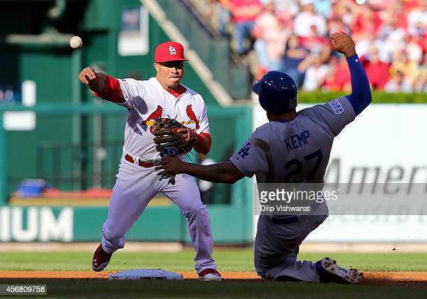 Matt Kemp of the Los Angeles Dodgers slides into second as Kolten Wong of the St Louis Cardinals turns a double play in the second inning in Game...