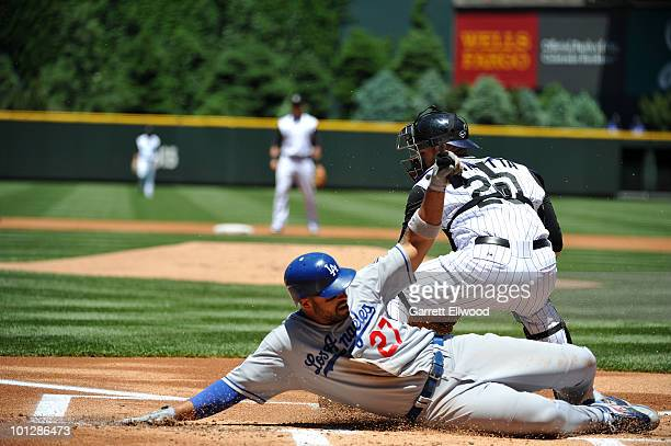 Matt Kemp of the Los Angeles Dodgers slides safely into home past Chris Iannetta of the Colorado Rockies during the game at Coors Field on May 30...