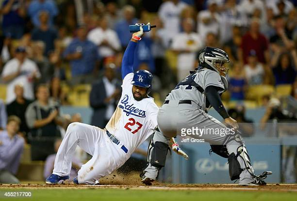 Matt Kemp of the Los Angeles Dodgers slides safely past catcher Rene Rivera of the San Diego Padres and scores a run in the second inning at Dodger...
