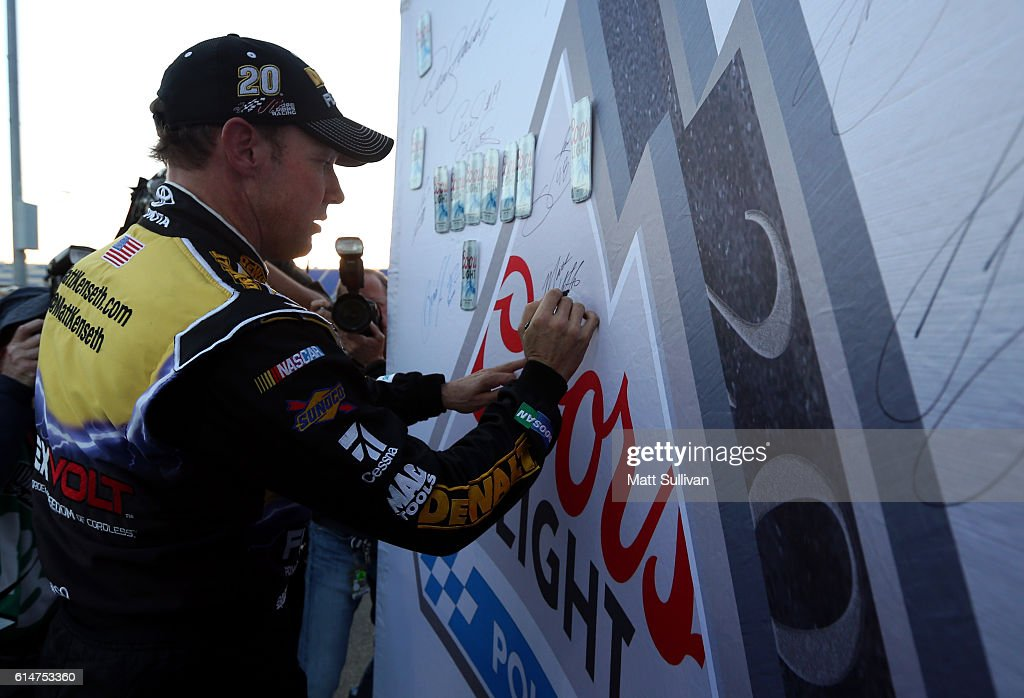 Matt Kenseth, driver of the #20 DEWALT FLEXVOLT Toyota, signs Coors Light Pole Award banner after qualifying in the pole position for the NASCAR Sprint Cup Series Hollywood Casino 400 at Kansas Speedway on October 14, 2016 in Kansas City, Kansas.