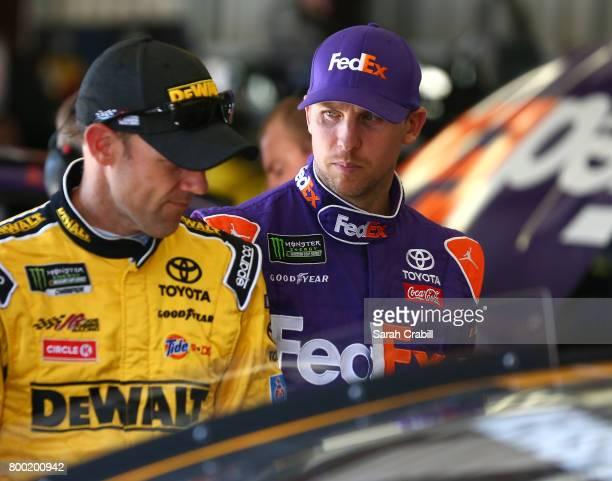 Matt Kenseth driver of the DeWalt Flexvolt Toyota talks to Denny Hamlin driver of the FedEx Ground Toyota in the garage during practice for the...
