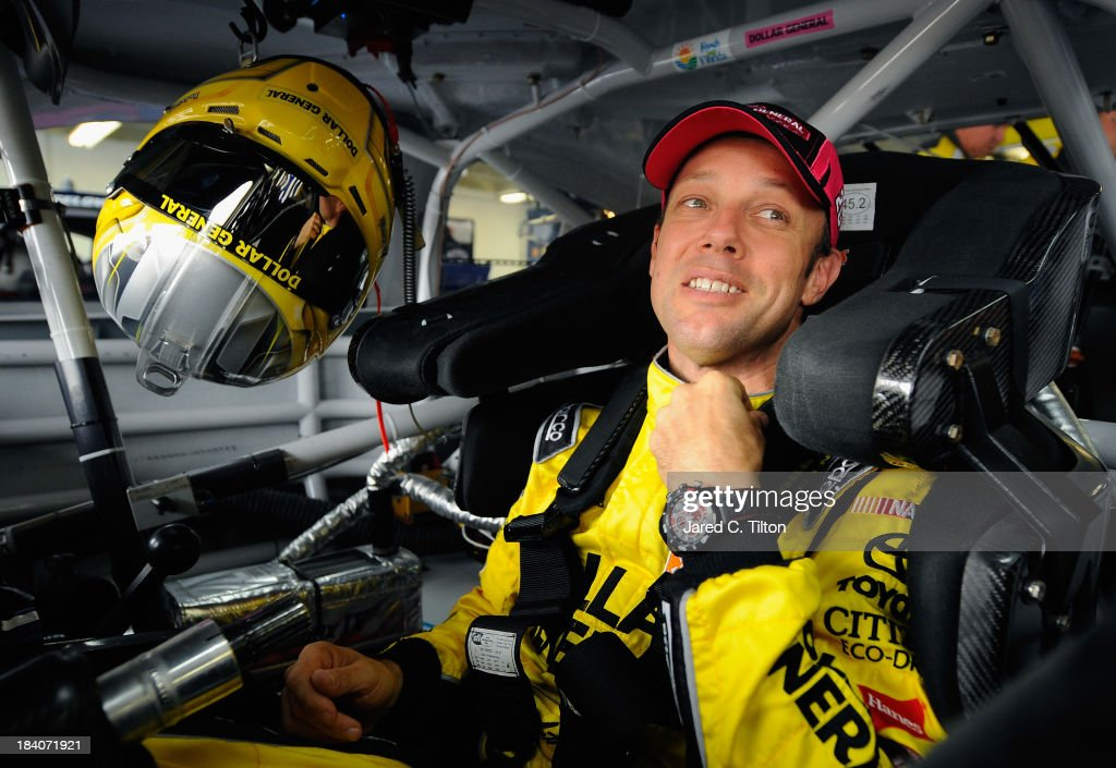 Matt Kenseth, driver of the #20 Dollar General Toyota, adjusts his equipment in his car during practice for the NASCAR Sprint Cup Series Bank of America 500 at Charlotte Motor Speedway on October 11, 2013 in Concord, North Carolina.