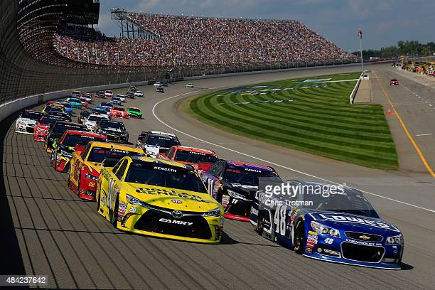 Matt Kenseth driver of the Dollar General Toyota and Jimmie Johnson driver of the Lowe's Chevrolet lead the field during the NASCAR Sprint Cup Series...