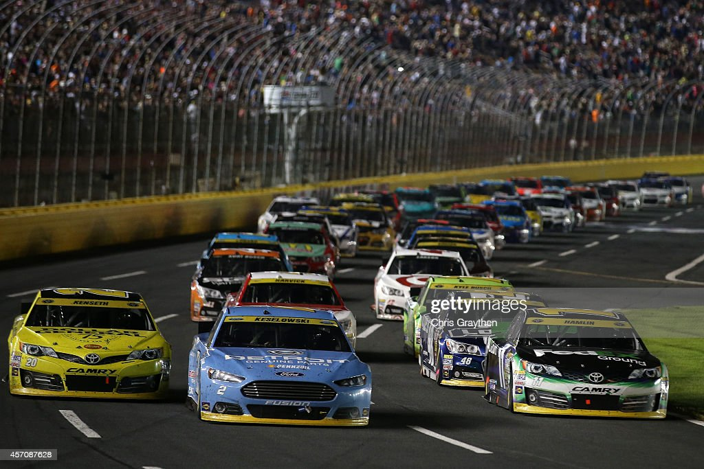 Matt Kenseth, driver of the #20 Dollar General Toyota, Brad Keselowski, driver of the #2 Detroit Genuine Parts Ford, and Denny Hamlin, driver of the #11 FedEx Ground Toyota, lead the field at a restart during the NASCAR Sprint Cup Series Bank of America 500 at Charlotte Motor Speedway on October 11, 2014 in Charlotte, North Carolina.