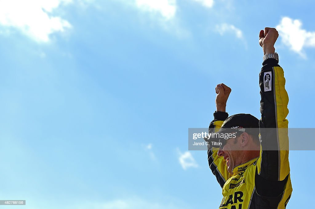 Matt Kenseth driver of the Dollar General Toyota celebrates in Victory Lane after winning the NASCAR Sprint Cup Series Windows 10 400 at Pocono...