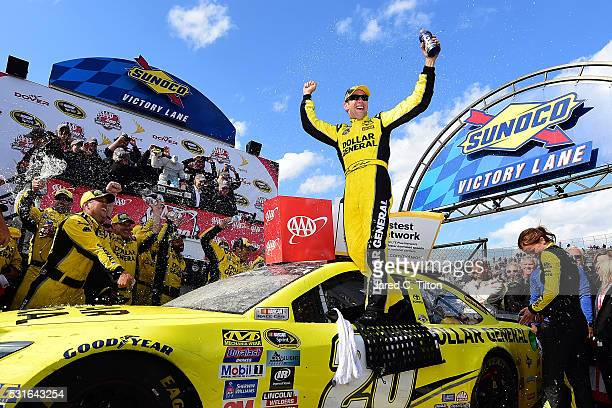 Matt Kenseth driver of the Dollar General Toyota celebrates in Victory Lane after winning the NASCAR Sprint Cup Series AAA 400 Drive for Autism at...