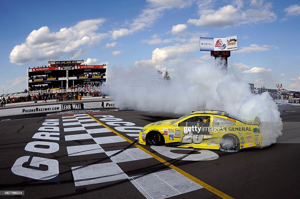 Matt Kenseth driver of the Dollar General Toyota celebrates with a burnout after winning the NASCAR Sprint Cup Series Windows 10 400 at Pocono...