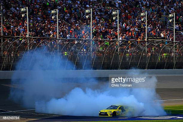 Matt Kenseth driver of the Dollar General Toyota celebrates with a burnout after winning the NASCAR Sprint Cup Series Pure Michigan 400 at Michigan...