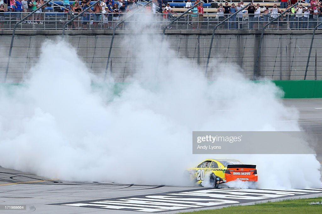 Matt Kenseth, driver of the #20 Dollar General Toyota, celebrates with the checkered flag after winning the NASCAR Sprint Cup Series Quaker State 400 at Kentucky Speedway on June 30, 2013 in Sparta, Kentucky.
