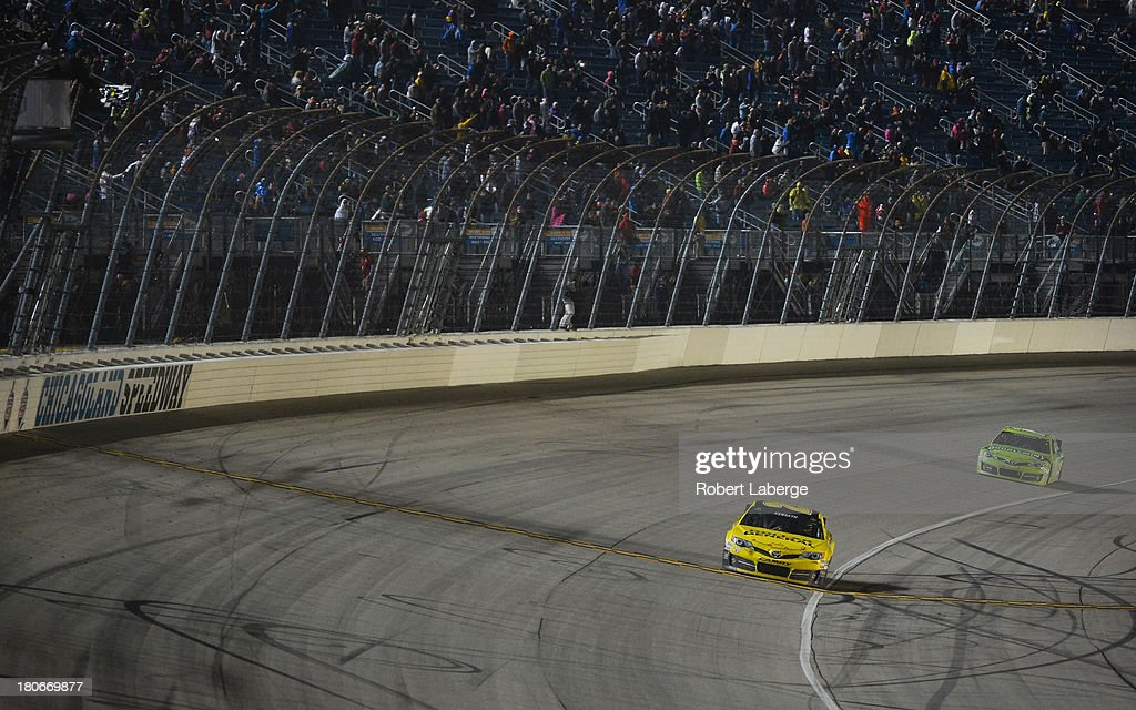 Matt Kenseth, driver of the #20 Dollar General Toyota, crosses the finish line to win the NASCAR Sprint Cup Series Geico 400 at Chicagoland Speedway on September 15, 2013 in Joliet, Illinois.