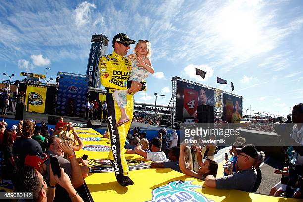 Matt Kenseth driver of the Dollar General Toyota holds his daughter Grace as he is introduced during prerace ceremonies for the NASCAR Sprint Cup...