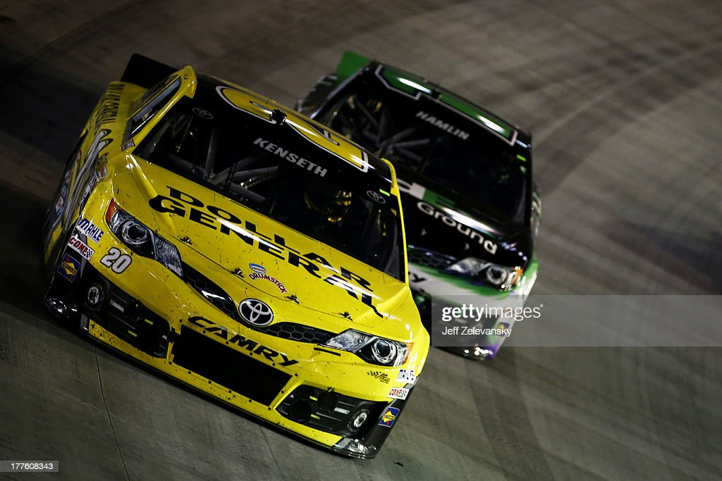 Matt Kenseth, driver of the #20 Dollar General Toyota, leads Denny Hamlin, driver of the #11 FedEx Ground Toyota, during the NASCAR Sprint Cup Series 53rd Annual IRWIN Tools Night Race at Bristol Motor Speedway on August 24, 2013 in Bristol, Tennessee.