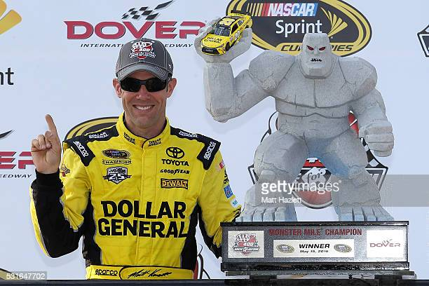 Matt Kenseth driver of the Dollar General Toyota poses with the trophy in Victory Lane after winning the NASCAR Sprint Cup Series AAA 400 Drive for...