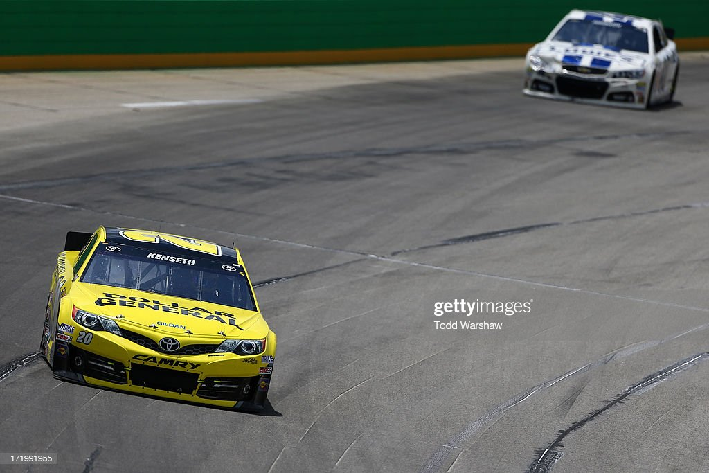 Matt Kenseth, driver of the #20 Dollar General Toyota, races Jimmie Johnson, driver of the #48 Lowe's Dover White Chevrolet, during the NASCAR Sprint Cup Series Quaker State 400 at Kentucky Speedway on June 30, 2013 in Sparta, Kentucky.