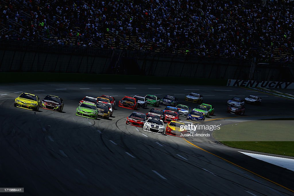 Matt Kenseth, driver of the #20 Dollar General Toyota, races out wide to take the lead from Jimmie Johnson, driver of the #48 Lowe's Dover White Chevrolet, on a restart during the NASCAR Sprint Cup Series Quaker State 400 at Kentucky Speedway on June 30, 2013 in Sparta, Kentucky.